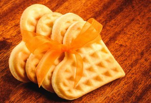Heart shaped cookies with orange ribbon on wooden surface
